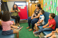 Woman speaking to children inside mobile literacy bus