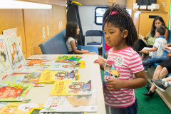 Child looks at literacy activities inside mobile literacy bus