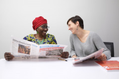Two women read newspapers while seated at table