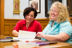 two women smiling while looking at paper