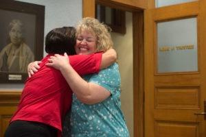 women hug in classroom