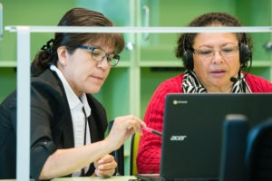 two women work at computer together