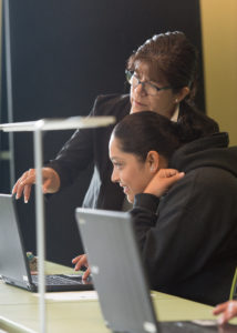 Two women work on computers together