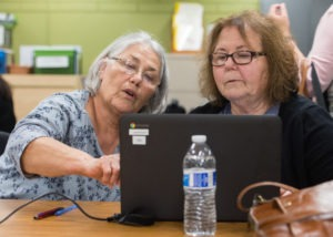 Two women look at computer screen together