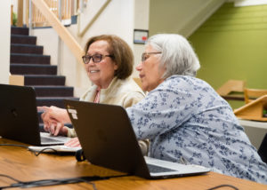 Two women work together on laptop