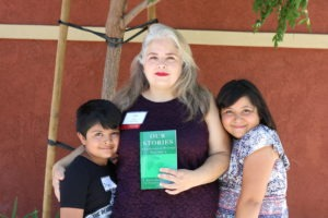 A woman holding a book and two children pose for a photo